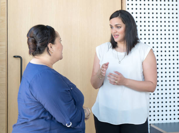 Candid portrait of business women having conversation in office meeting room. Females are of maori ethnicity. stock photo