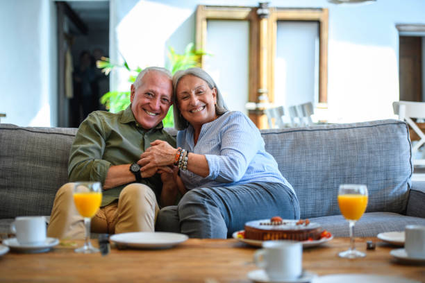 Candid Portrait of Compatible Senior Couple Relaxing at Home stock photo