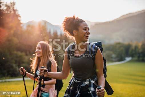 Front view with lens flare of mixed race and Caucasian female friends in 20s and 30s smiling as they enjoy late afternoon day hike.