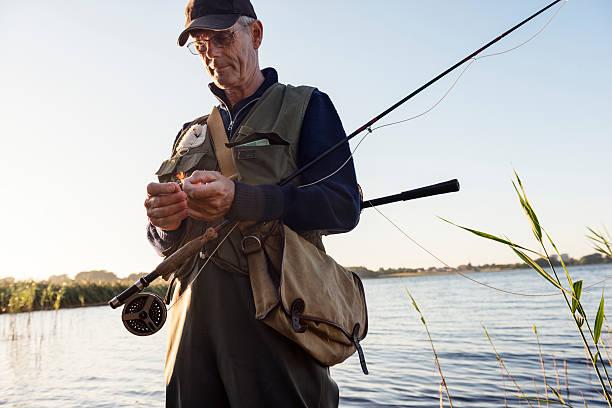 candid porträt eines fly fisherman binden einen fly - angeln dänemark stock-fotos und bilder