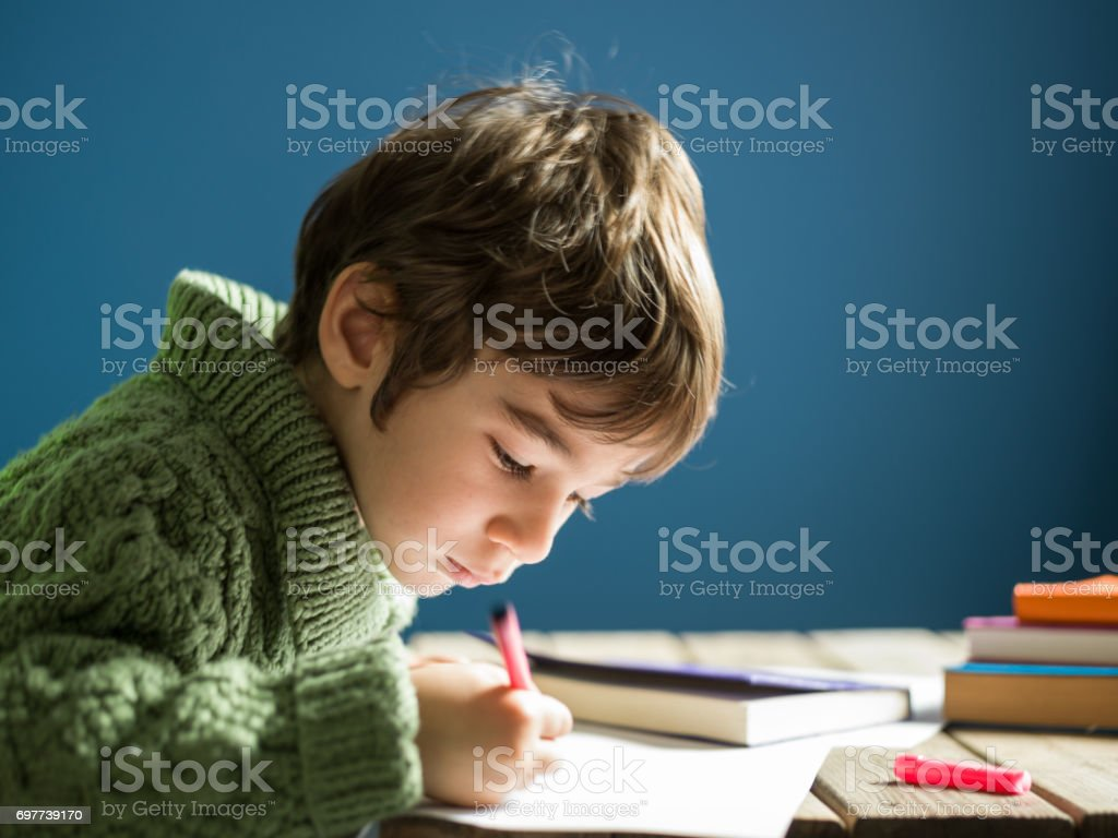 Candid portrait Of Little Boy Writing On Blank Paper On Desk stock photo