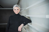 Mature woman with short grey hair wearing black sweater smiling towards the camera. Professional woman leaning against white wall with confident expression.