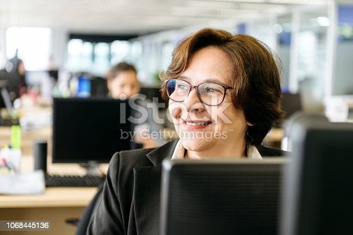 Cheerful businesswoman in her 50s smiling and looking away, using pc, sitting at her desk