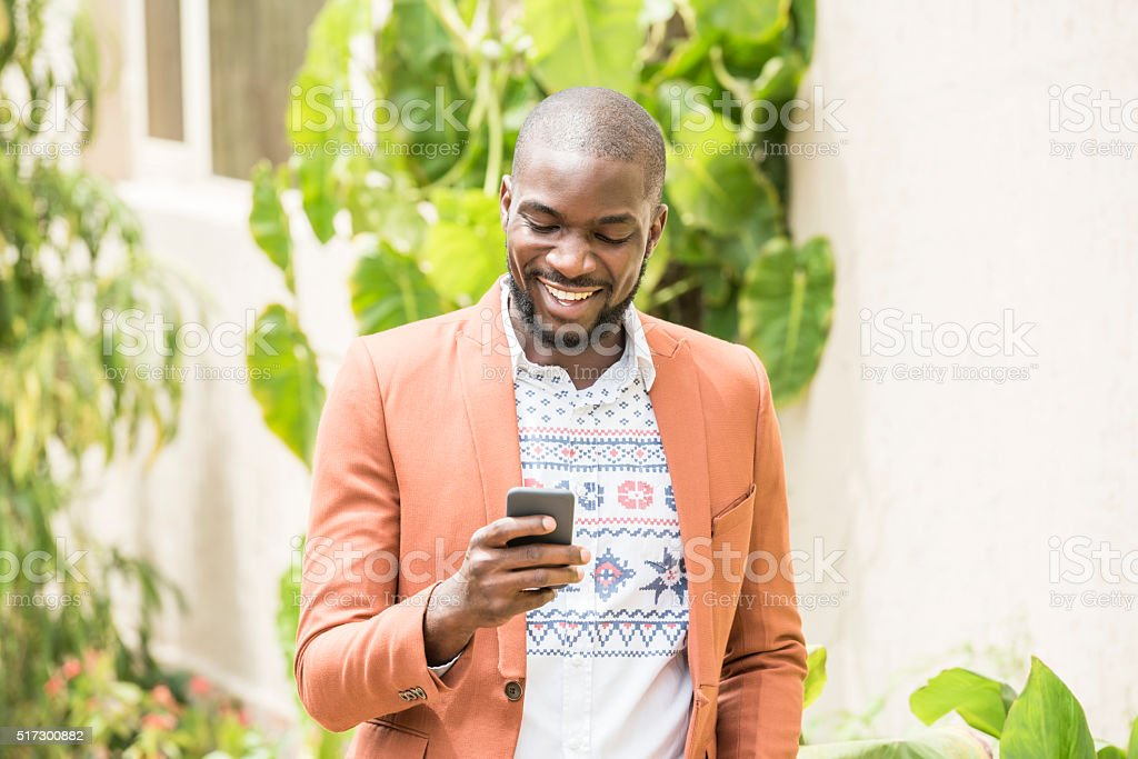 Candid portrait of Nigerian man using cell phone, smiling stock photo