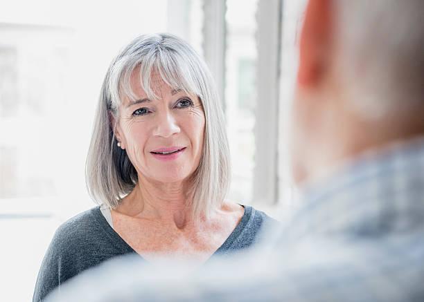 candid portrait of senior woman with grey bobbed hair - vrouw 60 stockfoto's en -beelden