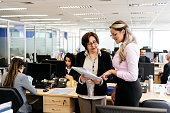 Mature woman with paperwork discussing with younger co-worker, explaining, conversation