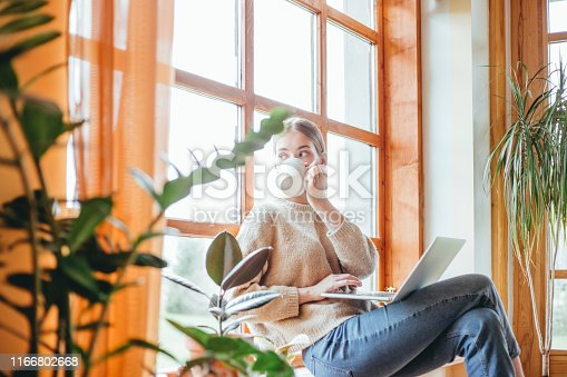 Young woman drinking coffee, while working on her laptop. She's sitting by the window.
