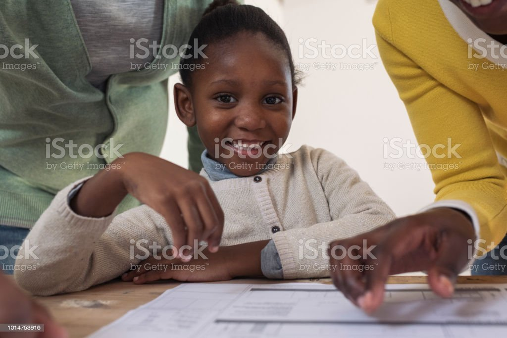 Candid portrait young African girl smiling to camera new house plans on the table in front of her stock photo