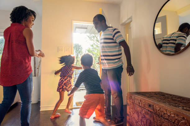 candid shot of african american family in hallway - leaving stock photos and pictures