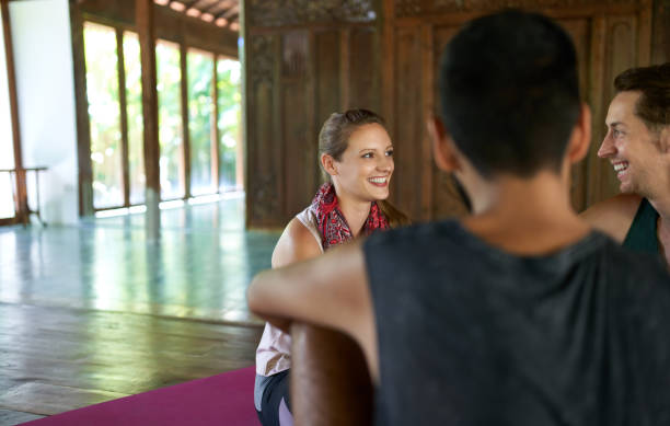 Candid shot of beautiful female meditation teacher discussing with mixed-race male students about yoga course and Indonesian culture in Bali stock photo