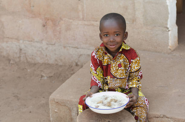 Candid Shot of Little Black African Boy Eating Rice Outdoors Candid Shot in Bamako, Mali. Showing local African ethnicity people in an image concept. hungry child stock pictures, royalty-free photos & images