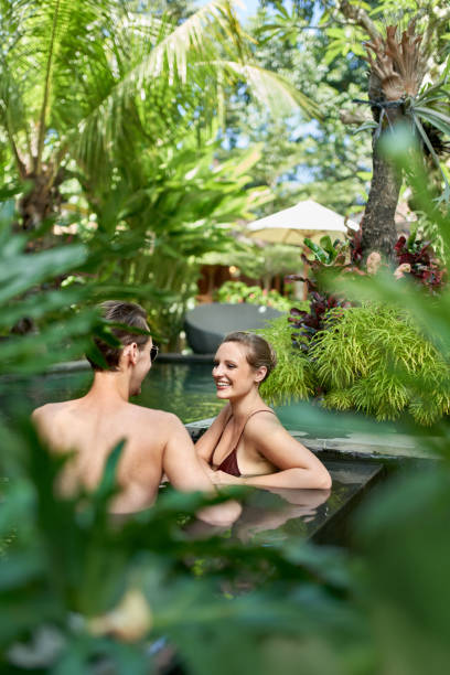Candid shot of two happy people relaxing together in lush resort pool of luxurious hotel in tropical Bali during retreat stock photo