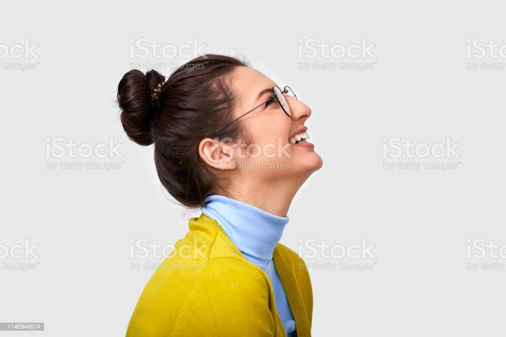 01b125170 Candid vista lateral estudio retrato de hermosa mujer joven, sonriendo  ampliamente, lleva traje casual