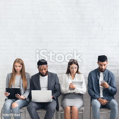 istock Candidates waiting for job interviews, sitting in row 1084111544