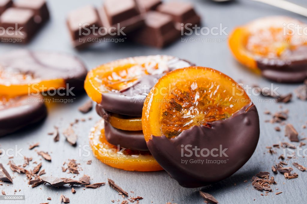 Candied orange slices in chocolate. Slate background stock photo