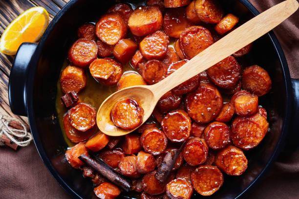 gecandiseerde yams, thanksgiving zoete aardappelen gekookt met kaneel, bruine suiker en boter - geglazuurd stockfoto's en -beelden