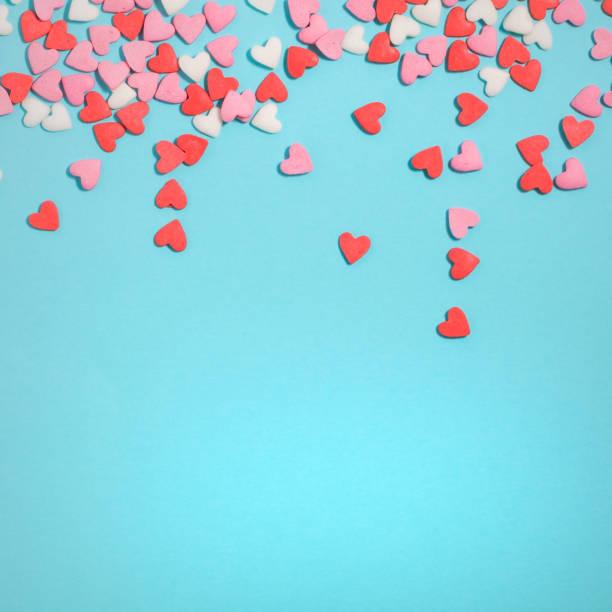 Doces corações de cores pastel sobre papel azul. Plano de leigos. - foto de acervo