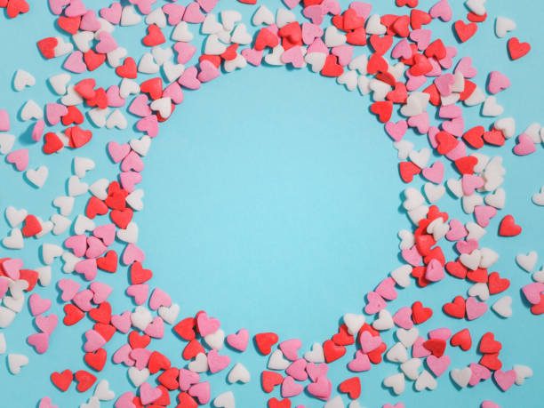 Candies hearts of pastel colors on blue paper. Flat lay. stock photo