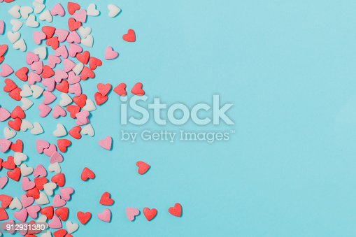 istock Candies hearts of pastel colors on blue paper. Flat lay. 912931380