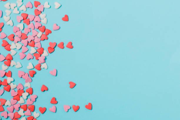 corazones de caramelos de colores pastel en papel azul. la endecha plana. - día de san valentín fotografías e imágenes de stock