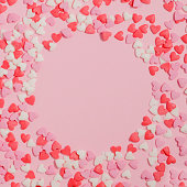 Candies hearts of pastel colors on pink paper. Flat lay. Copy space.