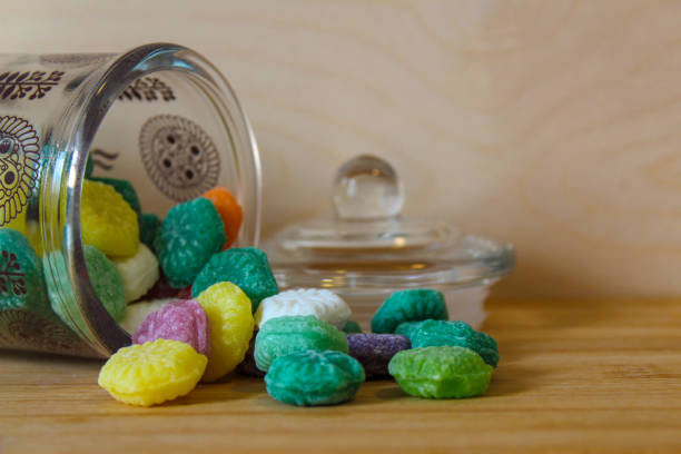 Candies spilled from jar stock photo