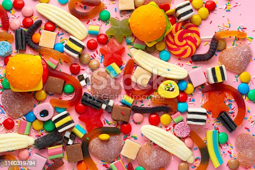 istock candies with jelly and sprinkles colorful array of different childs sweets and treats over pink like festive background 1160319794