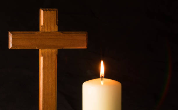 Candle an cross in darkness stock photo