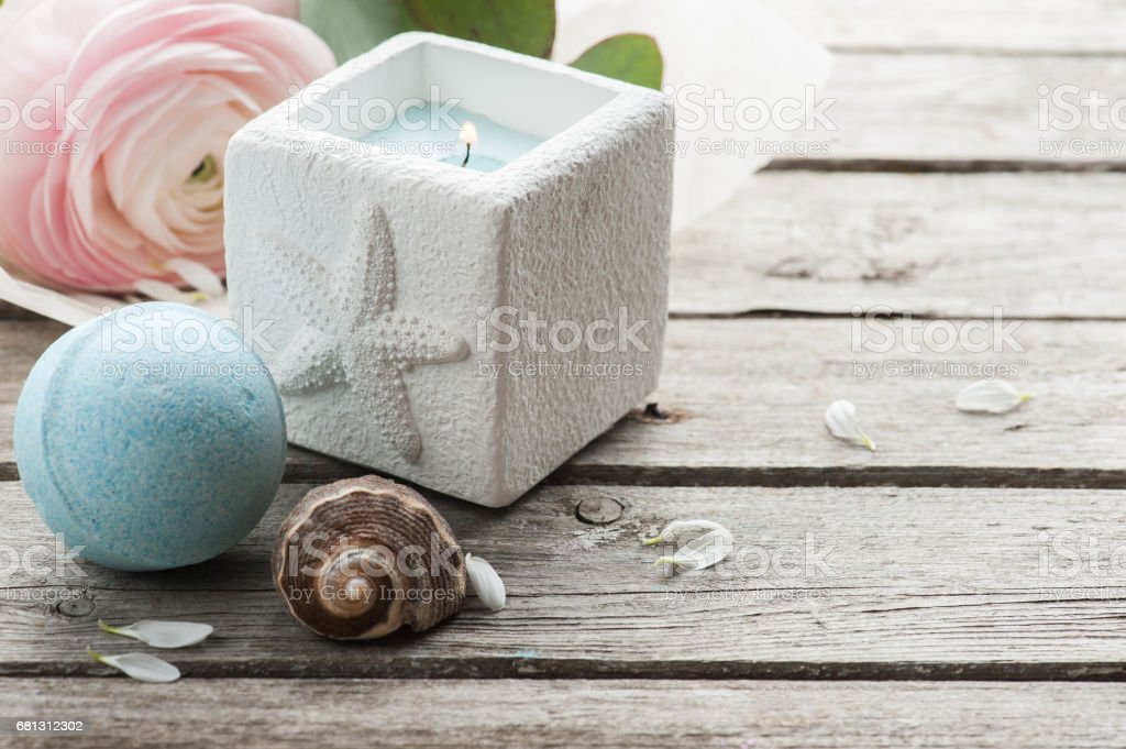 Candle and blue bath bomb over shabby wooden background royalty-free stock photo