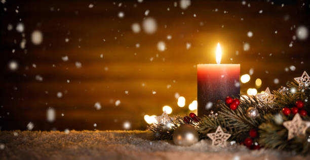 Candle and Christmas decoration with wooden background and snow stock photo