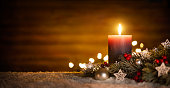 Candle and Christmas decoration with wooden background