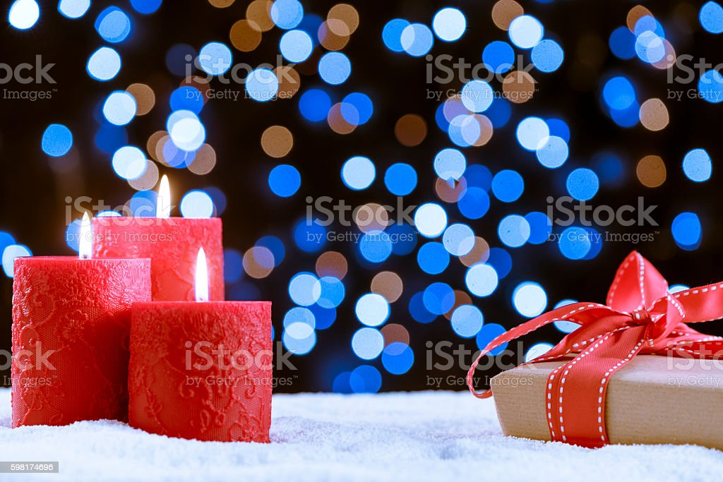 Candle and gift over snow for Christmas royalty-free stock photo