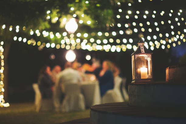 Candle and string lights outdoor dinner A string of fairy lights and a chandelier with candle hanging in-between trees photographed shining at night with image focus technique focus on the foreground bokeh background and dark and a table with peopleFranschhoek Cape Winelands South Africa grace stock pictures, royalty-free photos & images