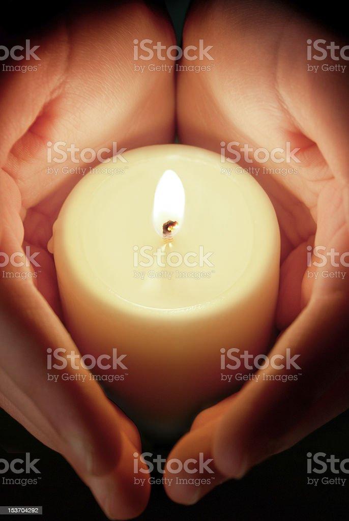 candle between hands stock photo