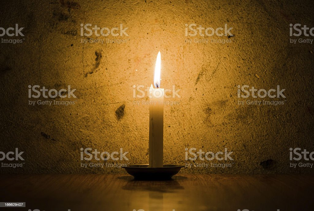 Candle burning, grungy wall background royalty-free stock photo