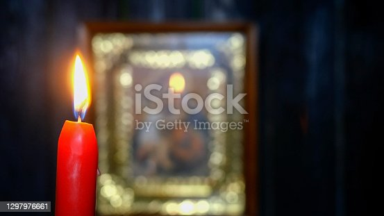 Candle burning in dark against soft focus Virgin Mary icon. Religion and spirituality. Selective focus. On dark wooden wall background. Close-up.