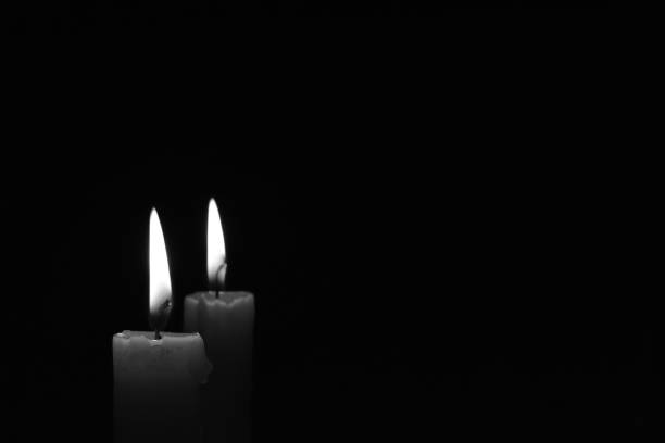 Candle burning in the black background. Black and white photo. Light candle burning brightly in the black background. Candle flame. Black and white photo. There's room for your text. The concept of mourning, grief or sorrow. mourning stock pictures, royalty-free photos & images