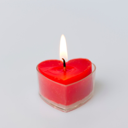 Close-up of a heart shape candle burning.