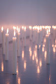 A low angle image of a huge group of wax candles all lit up with selective foreground focus Cape Town South Africa