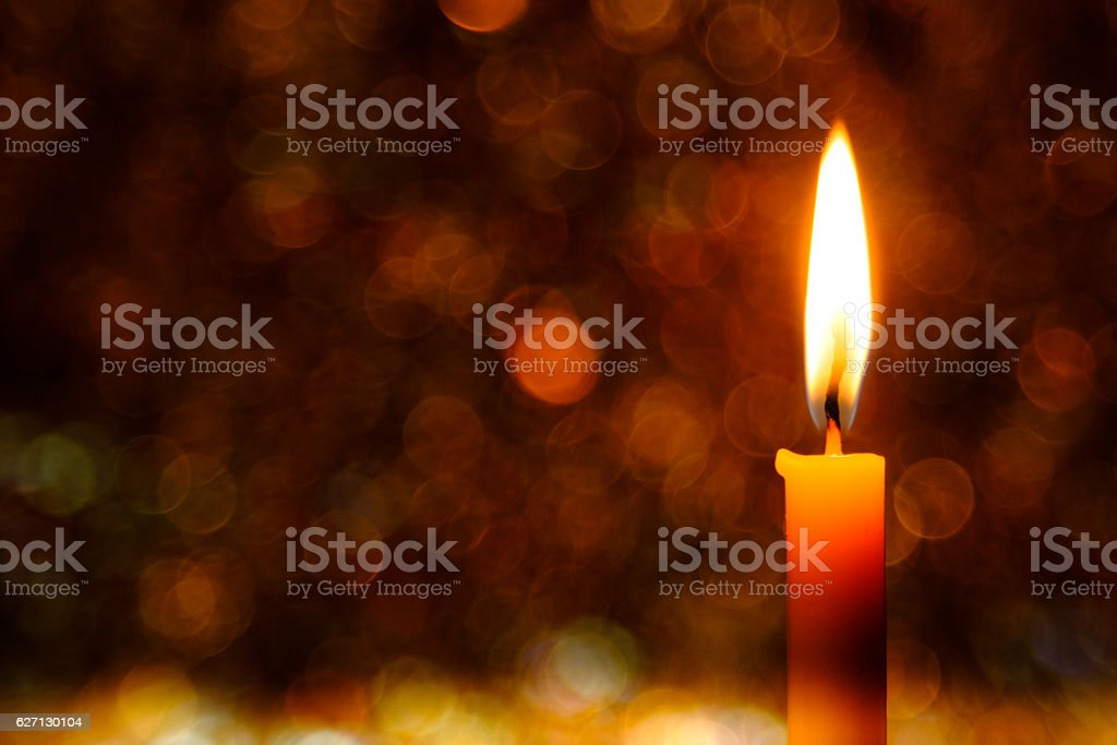Candle flame light at night with bokeh background Christmas lights.. stock photo