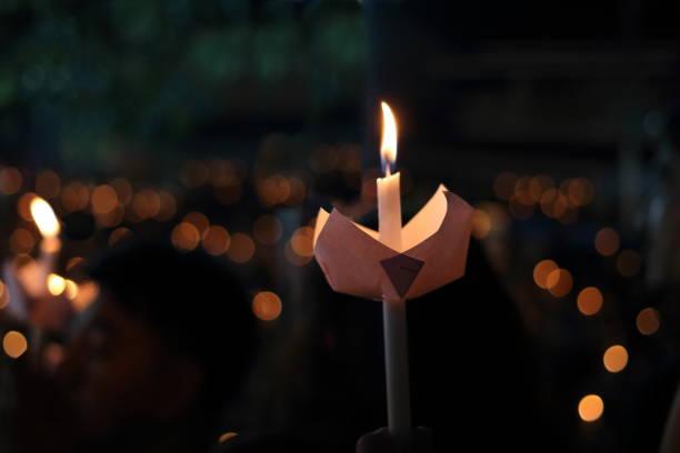llama de vela ligera en la noche con bokeh fondo. fondo abstracto de velas. - duelo fotografías e imágenes de stock