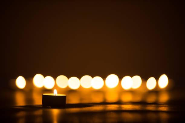 vela las llamas que brillan intensamente en la oscuridad. - duelo fotografías e imágenes de stock