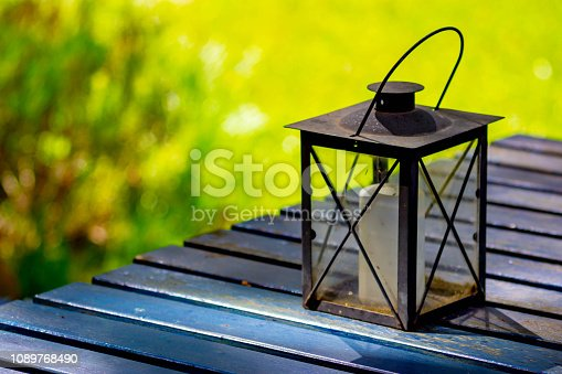 Candle holder on garden furniture in a garden/park setting in shade in Copenhagen, Denmark. The candle is inside a glass carrier.