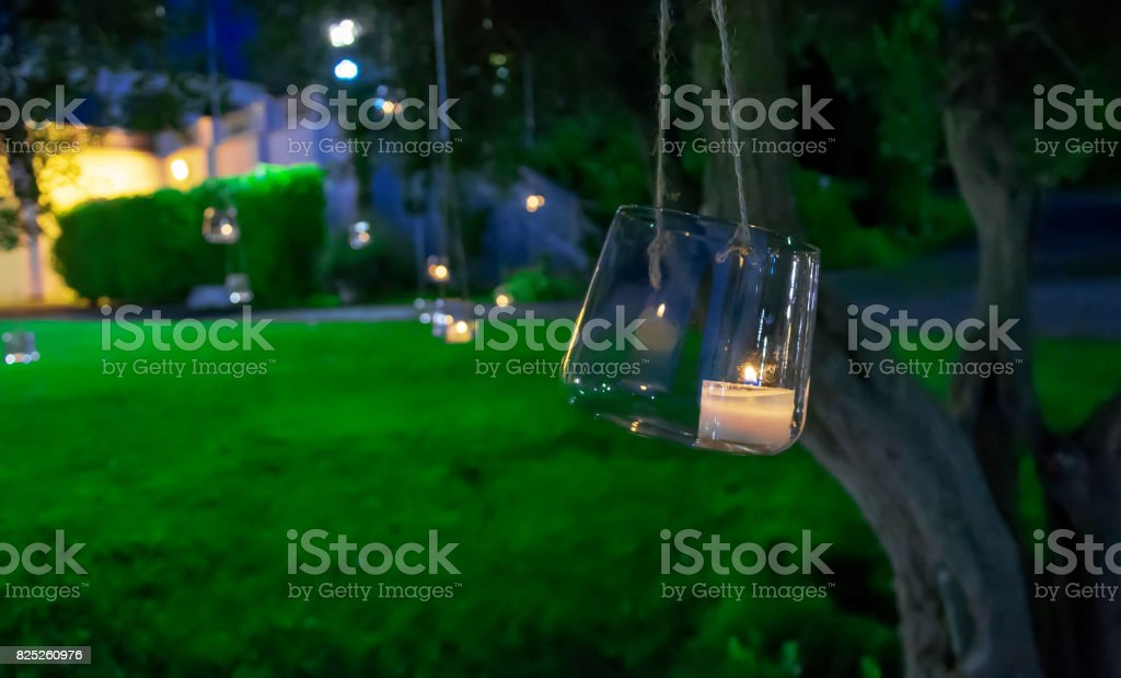 candle in a glass hanging from a tree stock photo