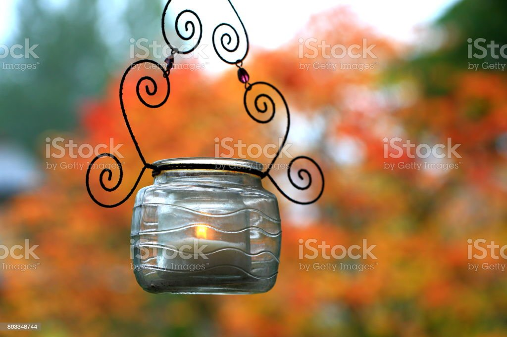 Candle in a glass hanging on tree stock photo