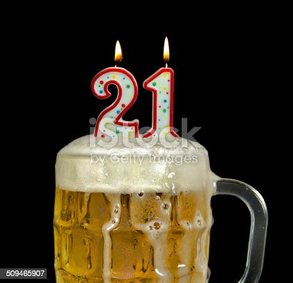 Birthday candles in beer mug for 21st birthday isolated on black.