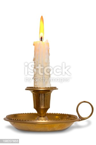 A dripping wax candle burning with flame in a traditional brass holder known as a chamberstick, isolated on a white background.