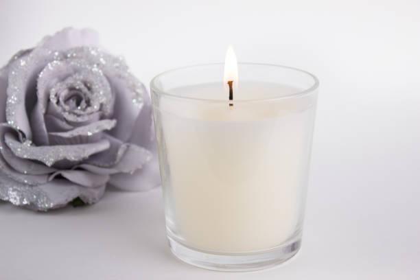 kerze in glas auf weißem hintergrund mit einer rose, produkt-mock-up - wachsblume stock-fotos und bilder
