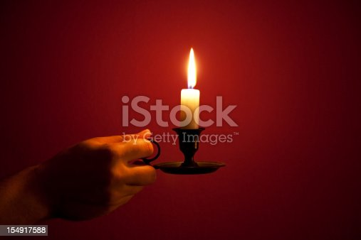 burning candle in a human hand