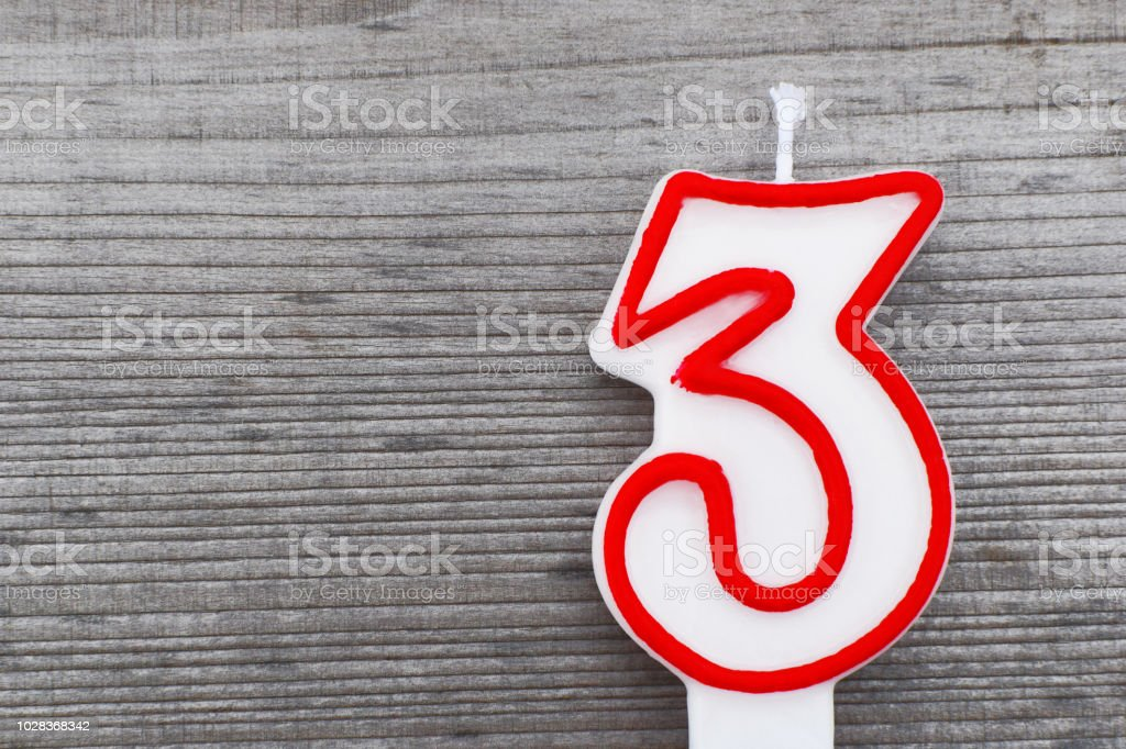 Candle in shape of number 3 stock photo